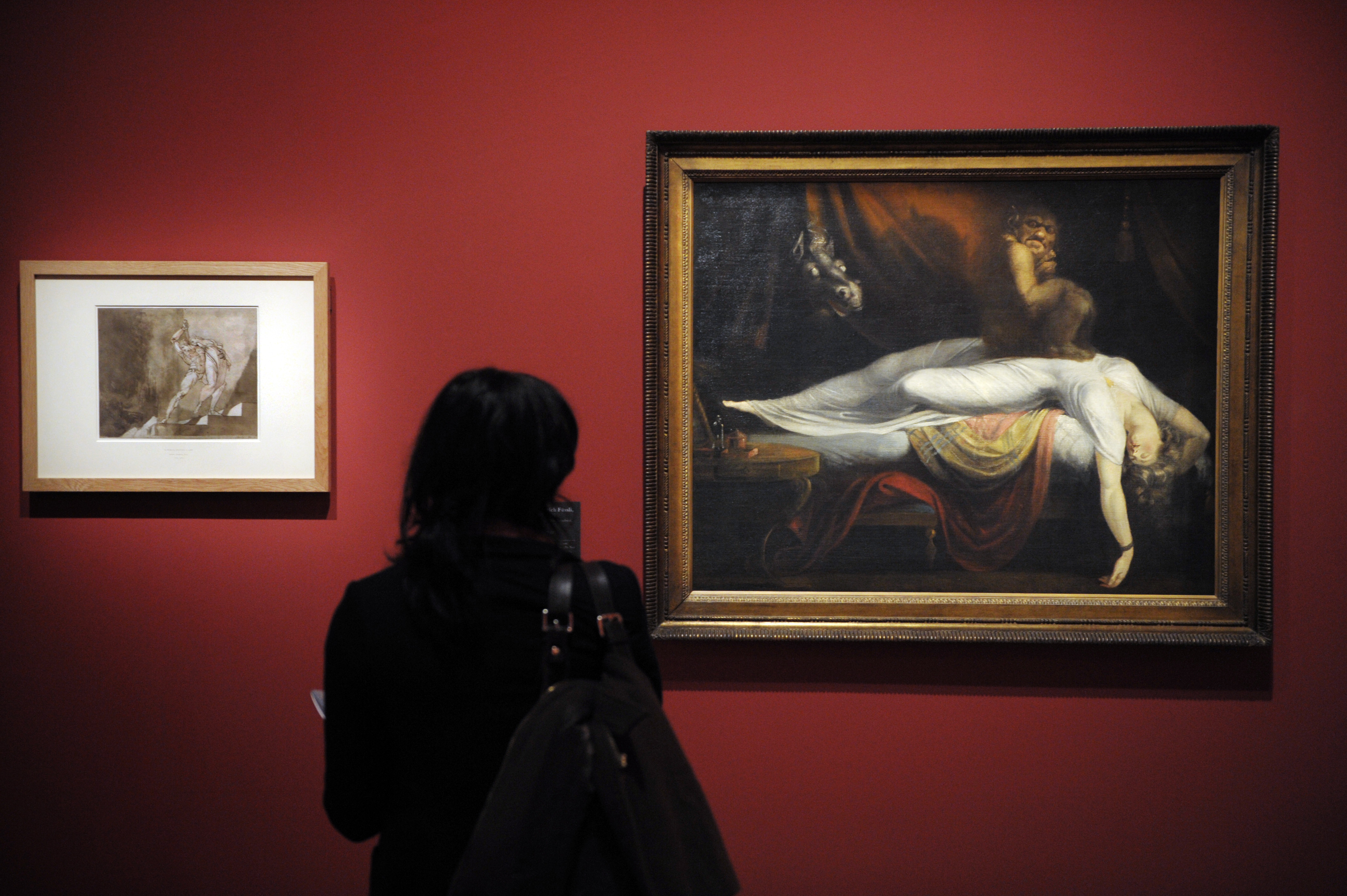 A woman looks at a painting by Johann He