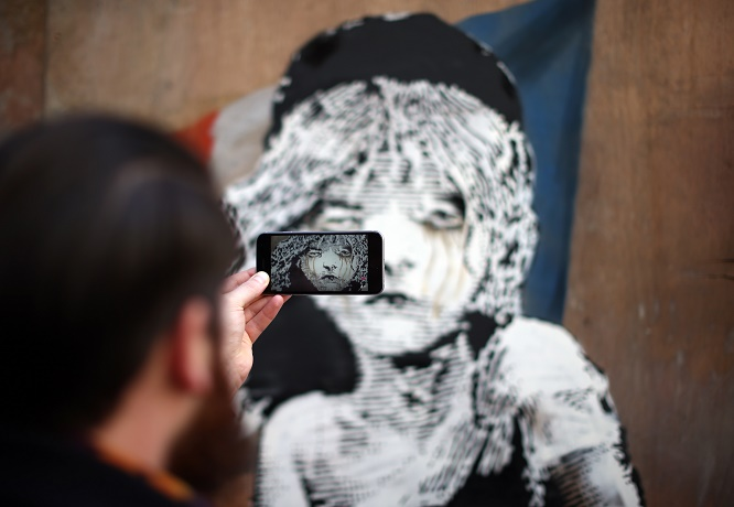 LONDON, ENGLAND - JANUARY 25: A passer-by takes a photograph of a Banksy artwork opposite the French embassy on January 25, 2016 in London, England. The graffiti, which depicts a young girl from the musical Les Miserables with tears in her eyes as CS gas moves towards her, criticises the use of teargas in the 'Jungle' migrant camp in Calais. (Photo by Carl Court/Getty Images)