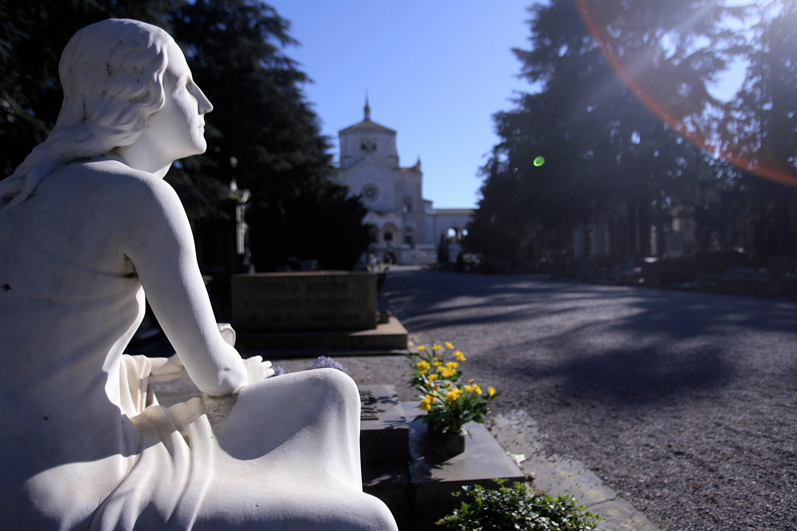 Sun shines on a tomb in central Milan's