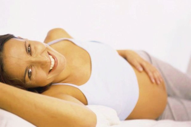 Pregnant Woman Lying Down --- Image by © ImageShop/Corbis