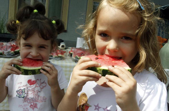 Children eat slices of watermelon in the