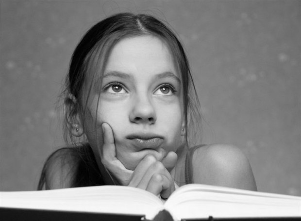 Very beautiful girl with an open book falls into a reverie
