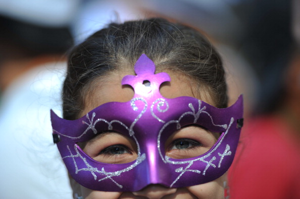 A little girl poses with her mask during