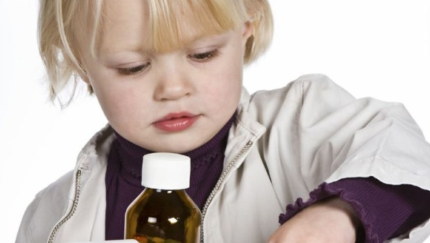 Little girl playing a dangerous game with medical pills