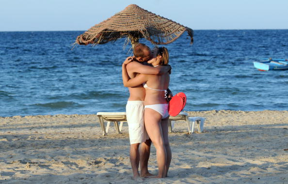 A couple embrace on the beach front of S