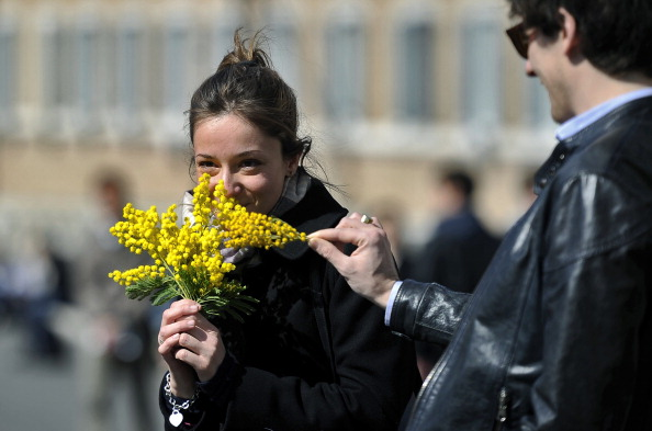 A woman holds a bunche of mimosaoutside