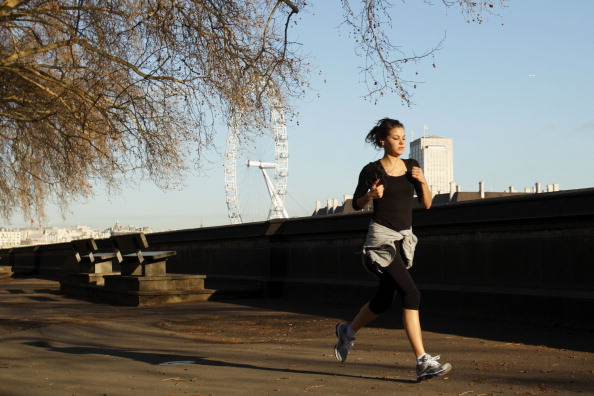 A woman jogs in the morning sunshine thr