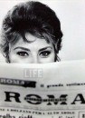 Alfred Eisenstaedt:  Actress Sophia Loren Peering Over the Top of a ROMA Newspaper