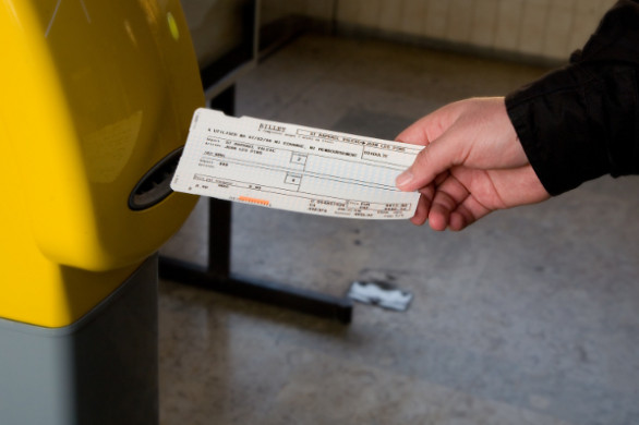 man punching the ticket before boarding on a French train station