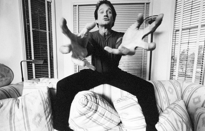 Actor/comedian Robin Williams standing on couch extending his hands at the camera like a crab.